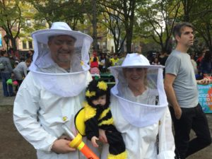 an adorable bee with two proud beekeepers