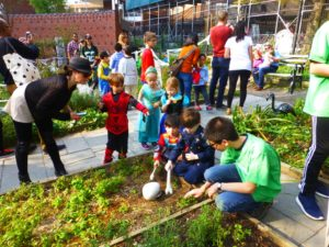 volunteer Theo showing children the haunted community garden